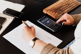 crop-woman-using-calculator-and-taking-notes-on-paper-4476375